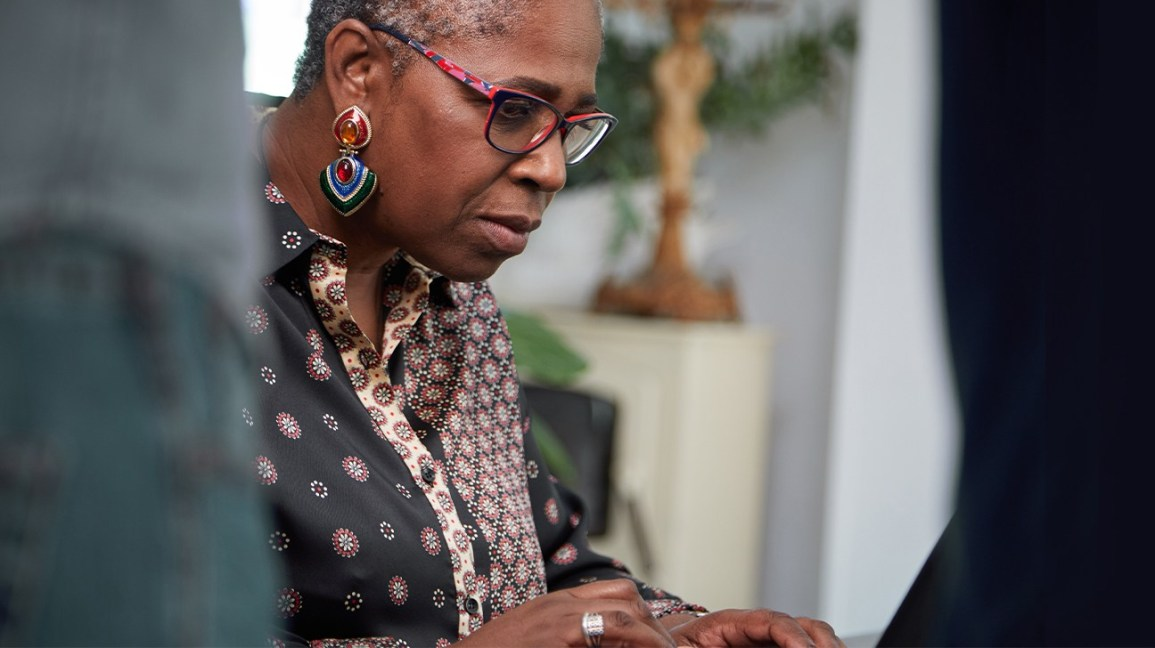 woman in glasses looking at a computer screen with her hands placed on the keyboard